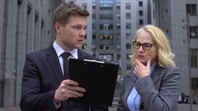 Travailleur de sexe masculin de société discutant des détails de contrat avec le collègue féminin mûr banque de vidéos