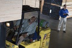 Travailleur de sexe masculin supérieur empilant les planches en bois Image libre de droits