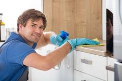 Travailleur de sexe masculin tenant le jet de bouteille et nettoyant la partie supérieure du comptoir Images stock