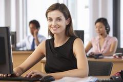 Travailleur de sourire dans le bureau occupé Photo stock