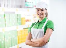 Travailleur de sourire de supermarché avec l'étagère sur le fond images stock