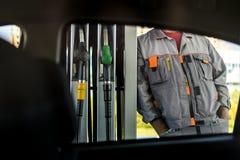 Travailleur de station service tenant les pompes proches de station de carburant, vue par la fenêtre de voiture photos libres de droits