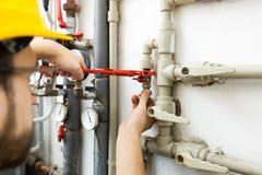 Travailleur de technicien réalisant les travaux d'entretien pour le syste de chauffage image stock
