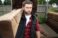 Travailleur de yard de bois de charpente, charpentier, choisissant, planches de transport seclecting de bois de construction photo libre de droits