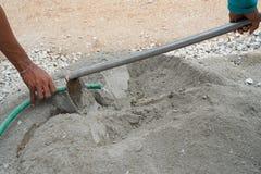 Travailleur deux mélangeant un ciment sur le plancher pour appliquer la construction Photo libre de droits
