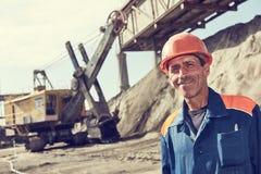 Travailleur devant le gravier lourd de chargement d'excavatrice dans le train photo stock