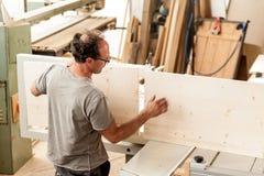 Travailleur du bois assemblant un meuble Photos libres de droits