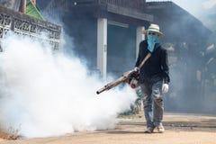 Travailleur embrumant le produit chimique pour éliminer le moustique à la rue Photos libres de droits