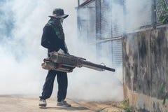 Travailleur embrumant le produit chimique pour éliminer le moustique à la rue Photo libre de droits