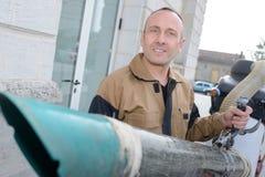 Travailleur employant le vide électrique de feuille dehors photographie stock libre de droits