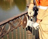 Travailleur en coupant le fer avec une machine électrique Photo libre de droits