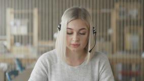 Travailleur en ligne de support technique Femme blonde avec des écouteurs sur la tête clips vidéos