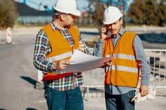 Travailleur et directeur de construction consultant sur un projet avec l'anglais photos stock