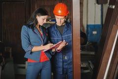 Travailleur et un chef féminin rendant compte les profils en métal photos stock