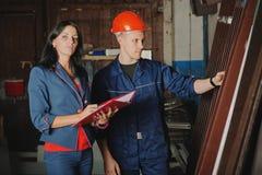 Travailleur et un chef féminin rendant compte les profils en métal Photo stock