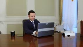 Travailleur européen dactylographiant sur le clavier et regardant le moniteur de l'ordinateur portable banque de vidéos