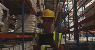 Travailleur féminin d'entrepôt patrouillant le couloir d'entrepôt la nuit 4k clips vidéos