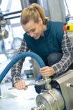 Travailleur féminin de brasserie avec les machines de mise en bouteilles sur l'usine photographie stock libre de droits
