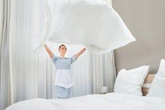 Travailleur féminin de ménage faisant le lit Image stock