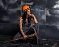 Travailleur féminin sexy de mineur avec la pioche, dans des combinaisons au-dessus de son corps nu, se reposant sur le plancher s Photographie stock libre de droits