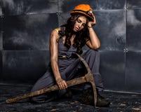 Travailleur féminin sexy de mineur avec la pioche, dans des combinaisons au-dessus de son corps nu, se reposant sur le plancher s Photo libre de droits
