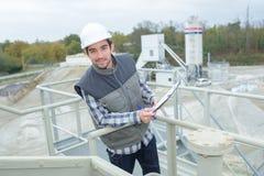 Travailleur faisant des contrôles de sécurité sur l'usine supérieure de silos image libre de droits