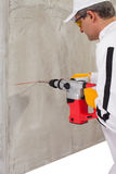 Travailleur faisant un trou avec un perforateur Image libre de droits