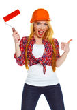 Travailleur féminin drôle de contruction dans un casque avec le rouleau à disposition Photos stock