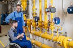 Travailleur handicap? dans le fauteuil roulant dans l'usine et le coll?gue photo libre de droits