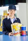 Travailleur heureux avec le maïs éclaté et boisson à la concession photo libre de droits