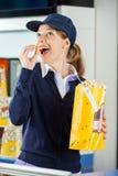 Travailleur heureux mangeant du maïs éclaté à la concession de cinéma photographie stock