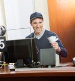 Travailleur heureux tenant des billets à la caisse image libre de droits