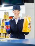 Travailleur heureux tenant le cinéma de maïs éclaté et de boissons photographie stock libre de droits