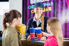 Travailleur heureux vendant des casse-croûte aux filles à la concession photographie stock