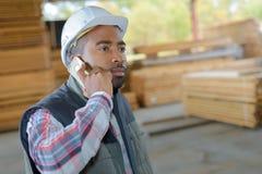 Travailleur industriel au téléphone sur la cour de bois de construction Photographie stock