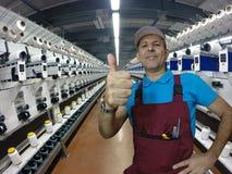Travailleur industriel dans le moulin de textile montrant des pouces  Images libres de droits