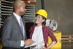 Travailleur industriel féminin regardant l'inspecteur masculin comme il écrit sur le presse-papiers image stock