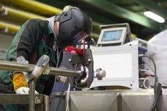 Travailleur industriel plaçant la machine de soudure orbitale photographie stock