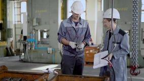 Travailleur industriel regardant au-dessus des détails un chef d'équipe sur une usine, la nouvelle livraison des pièces en métal clips vidéos
