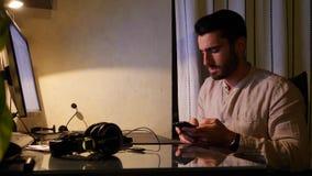 Travailleur inquiété s'asseyant au bureau à la maison occupé au téléphone clips vidéos