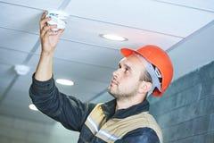 Travailleur installant le détecteur de fumée sur le plafond Image stock