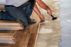 Travailleur installant les tableaux de plancher en bois photo stock