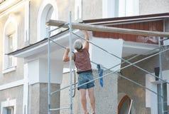 Travailleur installant les tableaux et le soffite de fasce de maison dehors photo libre de droits