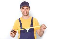 Travailleur jugeant un ruban métrique d'isolement sur le blanc Photos stock