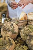 Travailleur local d'épicerie coupant en tranches le fromage photos libres de droits