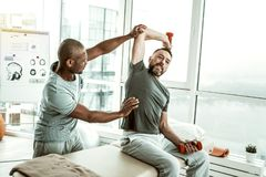 Travailleur médical conscient étirant le bras de son patient images stock