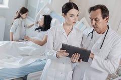 Travailleur médical sérieux consultant au-dessus du patient féminin image stock