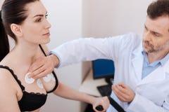 Travailleur médical soigneux appliquant des sondes sur le coffre de la femme Images stock