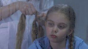 Travailleur médical tressant les cheveux bouleversés de fille, sentiment d'enfant nostalgique dans l'hôpital banque de vidéos
