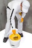 Travailleur mélangeant un plâtre à une truelle photo stock